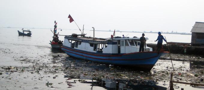 Messboot im verschmutzten Hafenwasser von Muara Angke, Jakarta